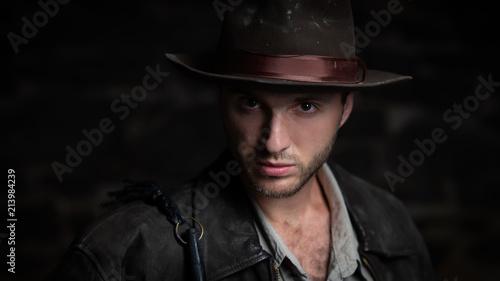 Photo adventurer (Indiana Jones). stone wall background.