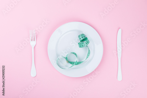 Diet Concept. Minimalism. Time to slim.Measuring tape with indicators in form of centimeters on  white Dish on a pink pastel Background. Top View. Flat Lay. Copy space for Text.