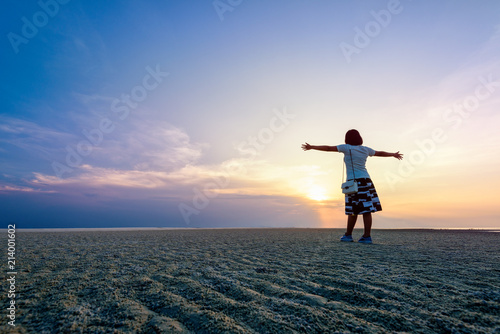 Fototapety, obrazy: Happy woman tourist arms outstretched on the beach watching the beautiful natural landscape of colorful sky and sea during sunset at Nathon Sunset Viewpoint in Samui island, Surat Thani, Thailand