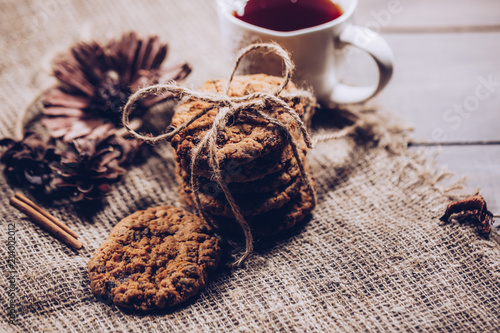 Tuinposter Koekjes Chocolate cookies on rustic wooden table and Sackcloth background. Chocolate chip cookies are stacked and tied with a rope. Food photography theme in vintage or retro color style.