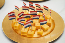 Dutch Cheese Cubes With Flags. Gouda Cheese Snack With A Dutch Flag On A White Table Background, Close-up