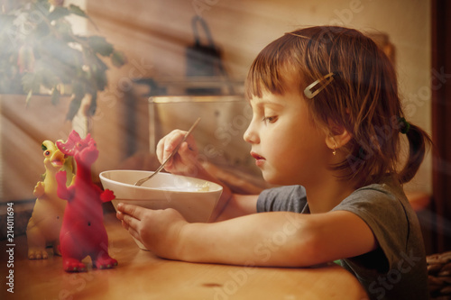 Little cute child girl eating noodles with dragon toys Wallpaper Mural