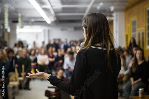 Fotografía  Woman gives a public speech in front of 200 people, in an industrial environment