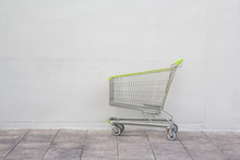 Green Steel Shopping Cart On Concrete Floor Background.