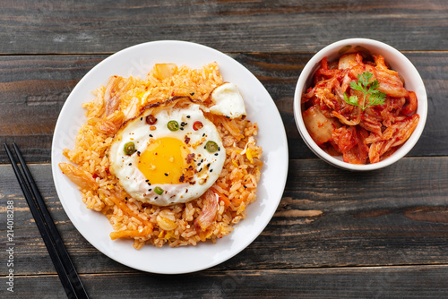 Kimchi fried rice with fried egg on top and fresh kimchi cabbage in a bowl on wooden background, top view, Korean food