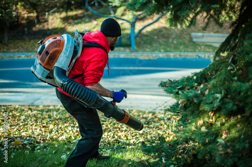 Photo Man holding a leaf blower in the grass, seen from right side