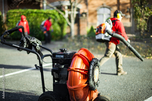 Lawn blower with workers holding leaf blowers in blurred background Canvas Print