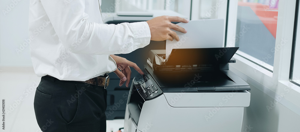 Photo Bussiness man Hand press button on panel of printer scanner or laser copy machin