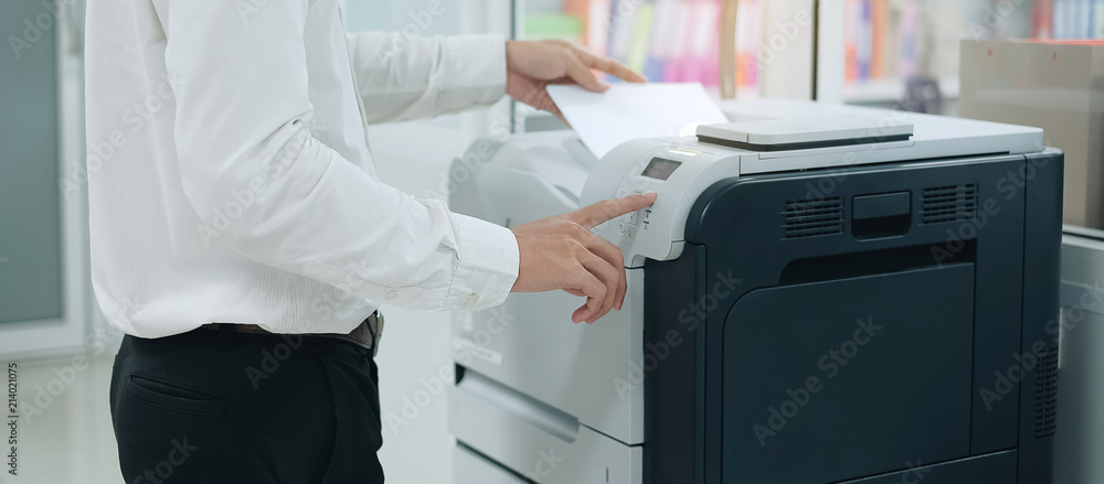Fototapety, obrazy: Bussiness man Hand press button on panel of printer scanner or laser copy machine in office