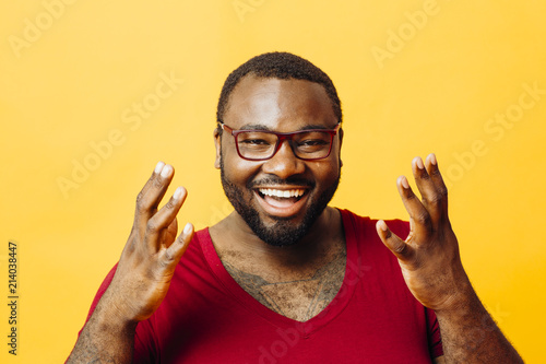 Fotografie, Tablou  Portrait of a very happy man with big smile and hands up, isolated on yellow bac