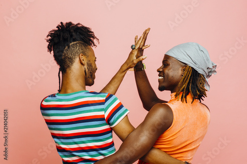 Photo Having fun in a relationship - portrait of two men holding hands and dancing