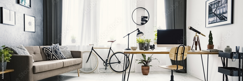 Fototapety, obrazy: An urban bicycle in a hipster living room interior with a big desk and computer in the workspace area and wooden furniture with industrial elements