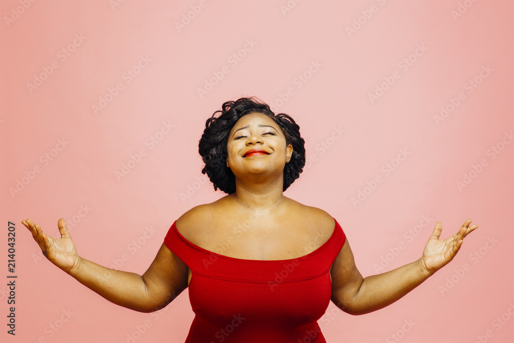 Fototapeta Life is wonderful/ Portrait of a confident, satisfied and happy woman with both hands out, isolated on pink