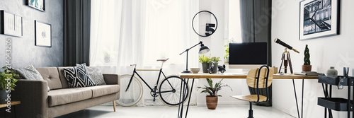 An urban bicycle in a hipster living room interior with a big desk and computer in the workspace area and wooden furniture with industrial elements