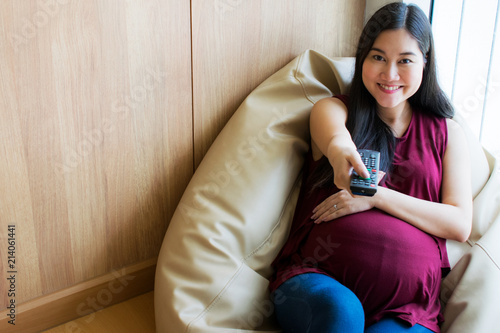 Surprising Happy Pregnant Woman Watching Tv Using A Remote Control And Beatyapartments Chair Design Images Beatyapartmentscom
