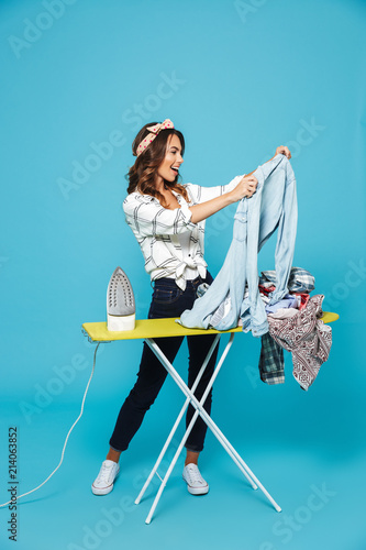 Obraz na plátně Full length portrait of european brunette housewife 20s ironing clean clothes on