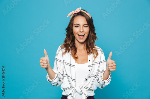 Obraz Portrait of lovely brunette woman 20s wearing headband smiling and showing thumbs up, isolated over blue background - fototapety do salonu