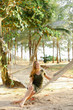 Young nice girl sitting barefoot on wicker hammock, sand and trees in background. Concep of resting in Thailand.