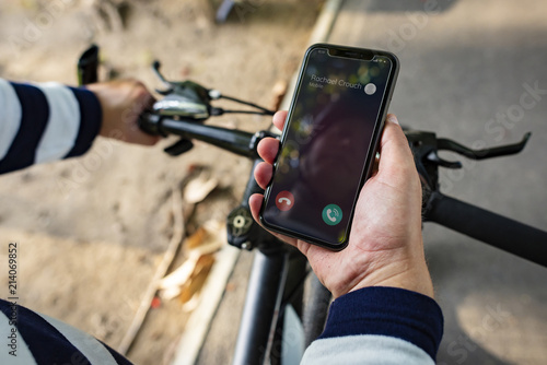 Foto  Biker holding smartphone with Incoming call
