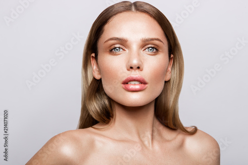 Beauty portrait of model with natural make-up. Fashion shiny highlighter on skin, sexy gloss lips make-up