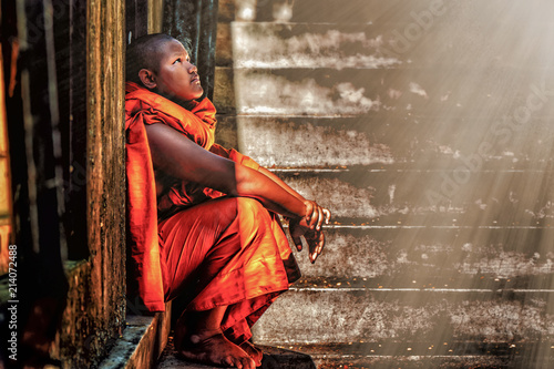Fotografia A Thai Buddhist novice sitting at old temple door close to stair steps looking u