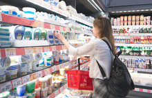 Young Girl With A Basket In Her Hands Chooses Cheese In The Milk Department Of The Supermarket. Woman Chooses Products In A Supermarket