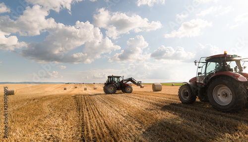 A tractor collecting straw bales