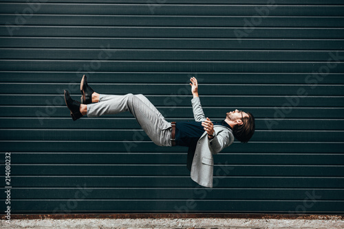 Fotografie, Obraz side view of handsome young businessman with briefcase falling in front of rolle