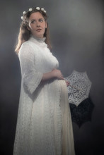 Historical Pregnant Brunette Woman In White Dress Holding Umbrella.