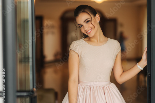 Obraz na plátně Stylish girl in dress stand in hotel hall. Girl smile to camera