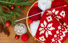 Winter Needlework. Handmade Christmas Gifts. Knitting A Warm Scarf With A New Year Red And White Pattern And A Spruce Branches With Festive Decorations On Wooden Table