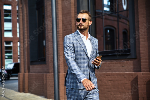 Portrait of sexy handsome fashion businessman model dressed in elegant checkered suit having business mobile conversation on smartphone on street Canvas-taulu
