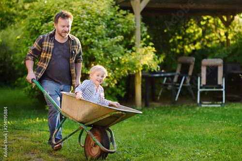 Fotomural  Happy little boy having fun in a wheelbarrow pushing by dad in domestic garden