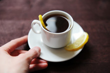 Espresso Romano Coffee With Lemon In A White Cup On A Dark Wooden Table. Hold In Hand Close Up