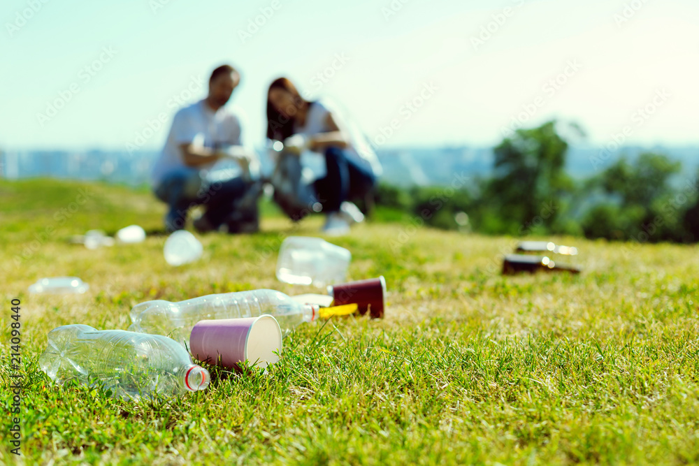 Fototapeta Lets clean it. Focused photo on rubbish that lying on the grass, attentive volunteers collecting plastic