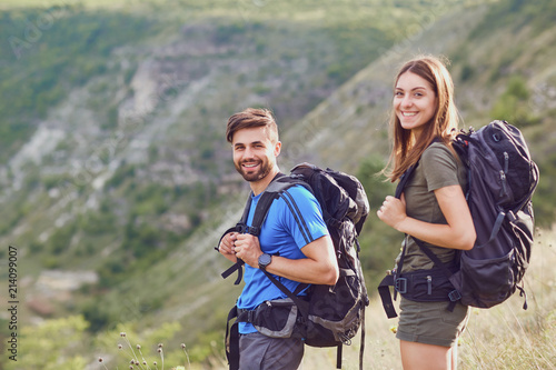 Fotografie, Tablou  Happy couple of tourists with backpacks smiling in nature.