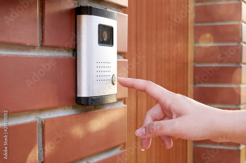 Vászonkép The female hand presses a button doorbell with intercom