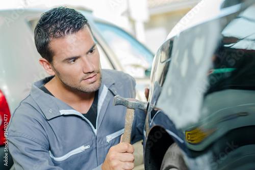 Mechanic panel beating a car Wallpaper Mural