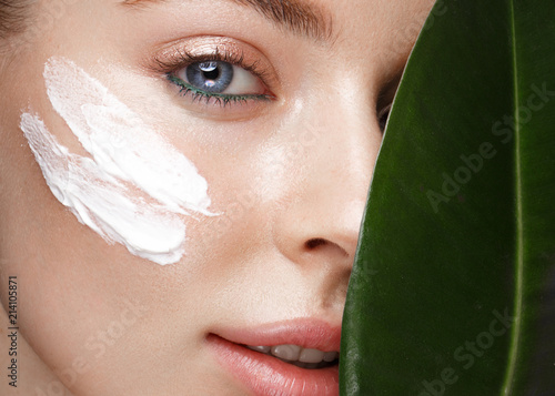 Cuadros en Lienzo Beautiful fresh girl with cosmetic cream on the face, natural make-up and green leaves