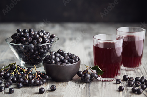 Fresh aronia berries and aronia berry juice in glasses Canvas Print