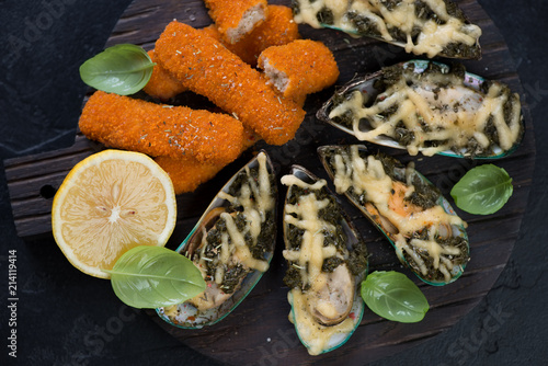 In de dag Assortiment Above view of mussels baked with spinach and cheese and roasted fish fingers on a wooden serving board, closeup