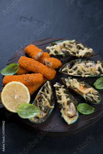 In de dag Assortiment Wooden serving board with seafood snacks including baked mussels and fried fish sticks, studio shot on a black stone surface