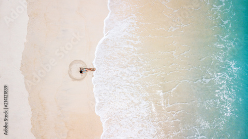 Poster Lieu connus d Asie Aerial view of young woman in blue bikini making sand angel. Hot beach with cool waves. Summer and holiday concept, seascape with girl, beach, beautiful waves, blue water. Top view from drone shot.