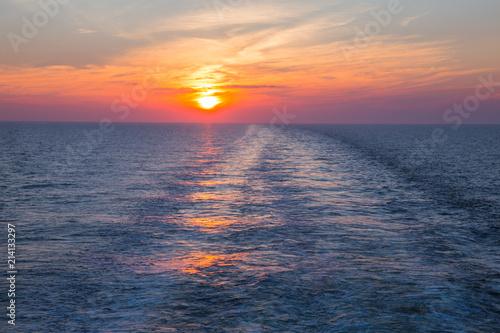 Spoed Foto op Canvas Zee zonsondergang Sunset and sea. Waves and nature. Orange sky.
