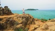 tourist girl is standing on the stone coast of the sea and looking into the distance to the waves and the island. enjoys the sea view and tropical adventure.