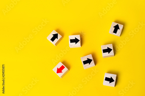 Fotografie, Obraz  Wooden blocks with red arrow facing the opposite direction black arrows, Unique, dissenting opinion, individual and standing out from the crowd