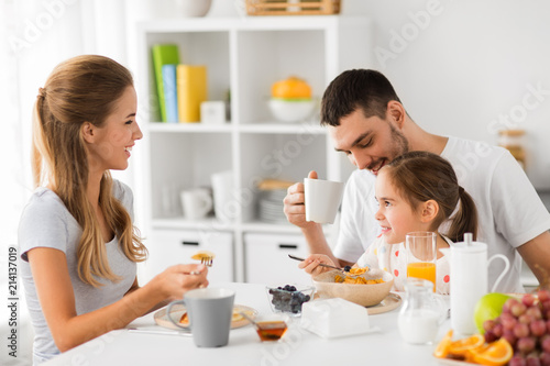Obraz na plátně  family, eating and people concept - happy mother, father and daughter having bre