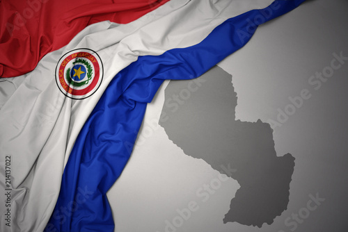 waving colorful national flag and map of paraguay. Canvas Print
