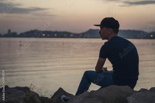 Pensive teen with black cap sitting on the rocks and looking to the sea Wallpaper Mural