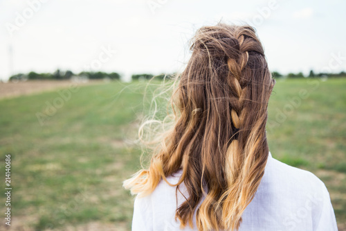 Foto auf AluDibond Olivgrun Portrait of young blonde from behind with carelessly braided pigtail and flying hair in wind in field.
